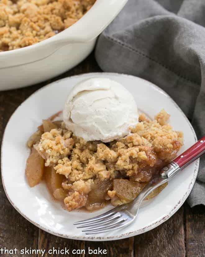 Easy Apple Crisp on a white plate topped with ice cream