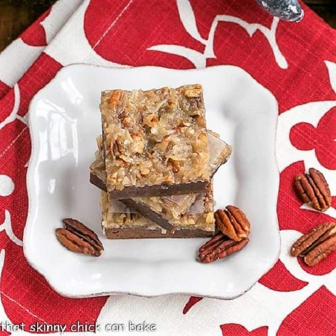 Overhead view of a stack of German Chocolate Brownies on a square white plate with pecan halves