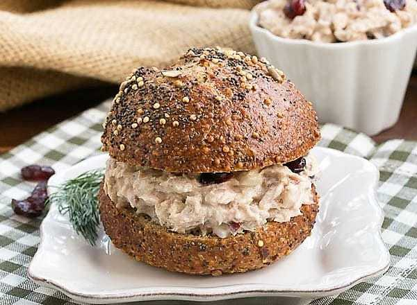 Tuna salad on a bun on a square white plate