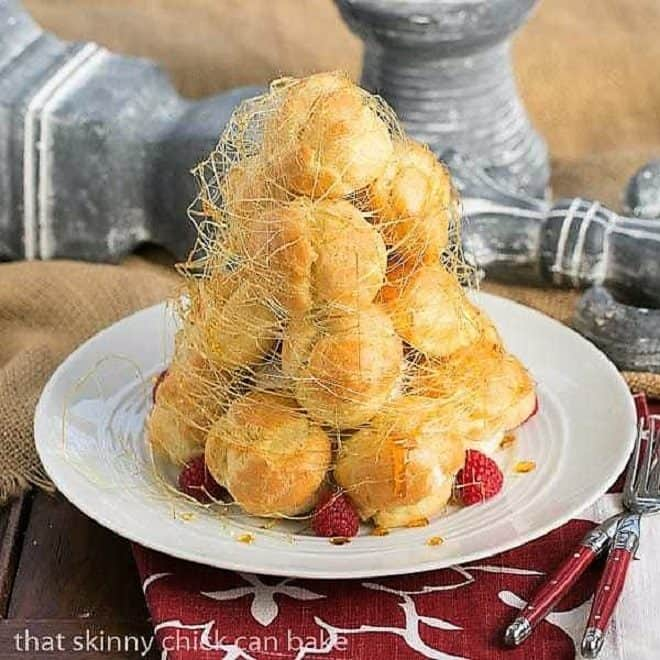 Lemon Cream Croquembouche on a white serving plate garnished with fresh raspberries and spun sugar