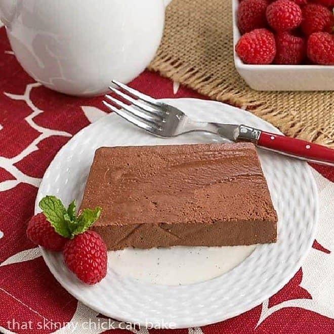 Marquise au Chocolat slice on a white dessert plate with a raspberry garnish