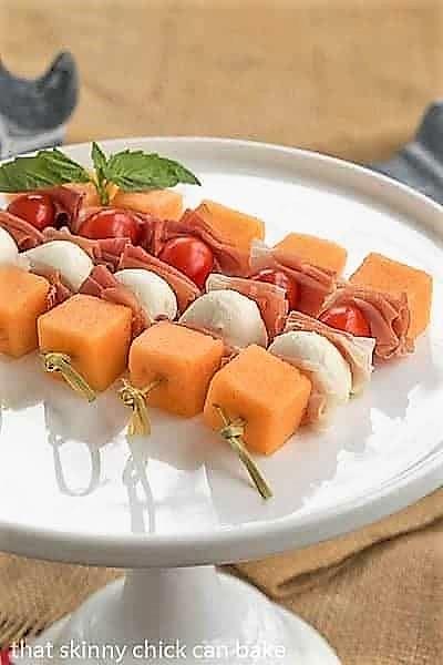 Melon and Prosciutto Skewers on a white ceramic cake stand
