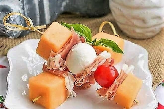 Melon and Prosciutto Skewers on a small white a