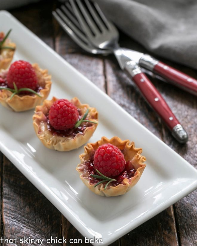 Baked Brie appetizers on a white serving tray