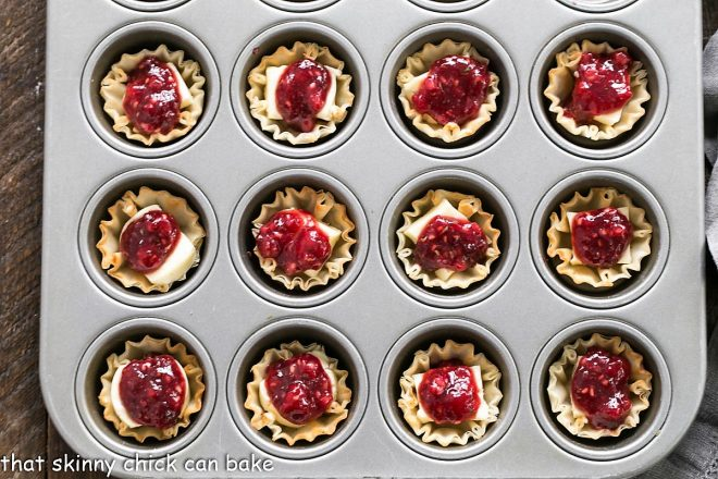 Unbaked Brie appetizers in a muffin tin