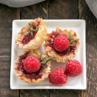 OVerhead view of a baked brie appetizer with raspberries and rosemary