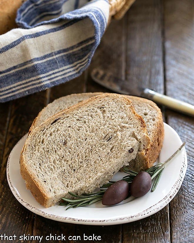 Rosemary Olive Bread slices on a white plate with fresh rosemary and olives