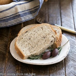 Sliced Rosemary Olive Bread on a small, white ceramic plate
