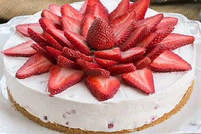 Strawberry Vanilla Cream Pie topped with fresh strawberry slices on a white Juliska serving plate