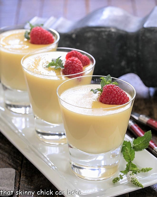 3 glasses of white chocolate pudding on a white tray garnished with fresh raspberries