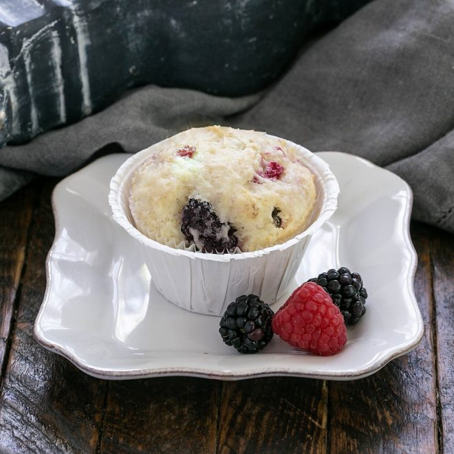 One berry muffin on a small white plate with a berry garnish