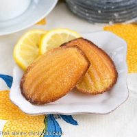Lemon Madeleines on a small white plate with lemon slices