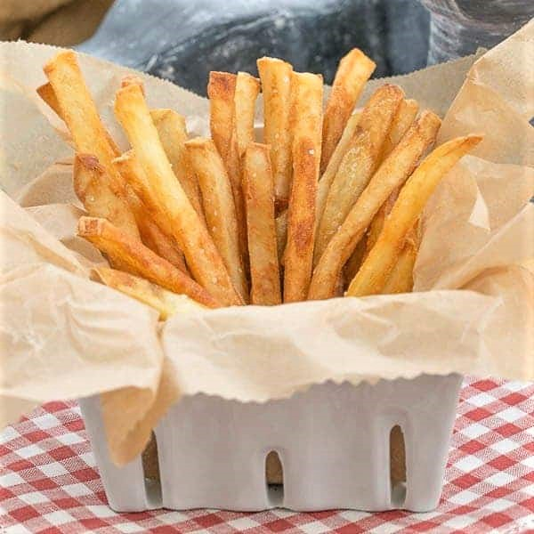 Thin Crispy French Fries in a ceramic basket lined with parchment