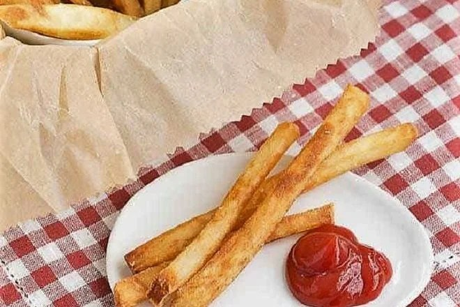 Thin Crispy French Fries on a white plate with a dollop of ketchup