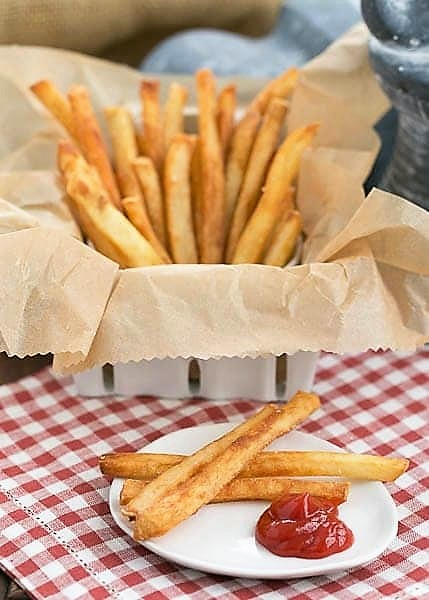 Thin Crispy French Fries in a basket on a checkered napkin with a plate with a few fries and a blob of ketchup