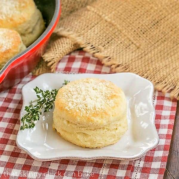 Buttermilk Goat Cheese Biscuits on a square white plate with a sprig of thyme
