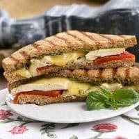 Chicken Pesto Grilled Cheese halves stacked on a white plate
