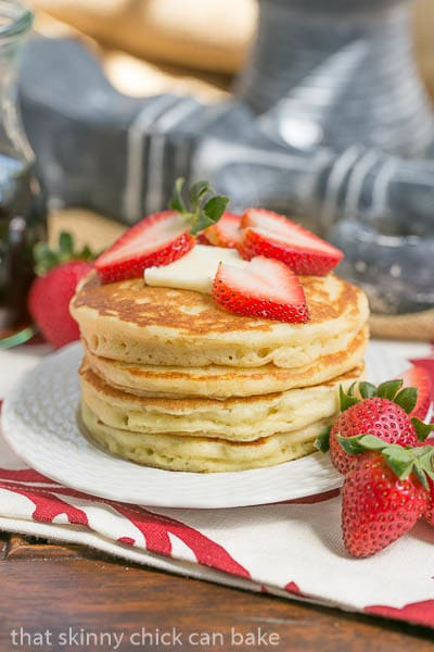 Classic Buttermilk Pancakes stacked on a white plate and topped with strawberries and a pat of butter