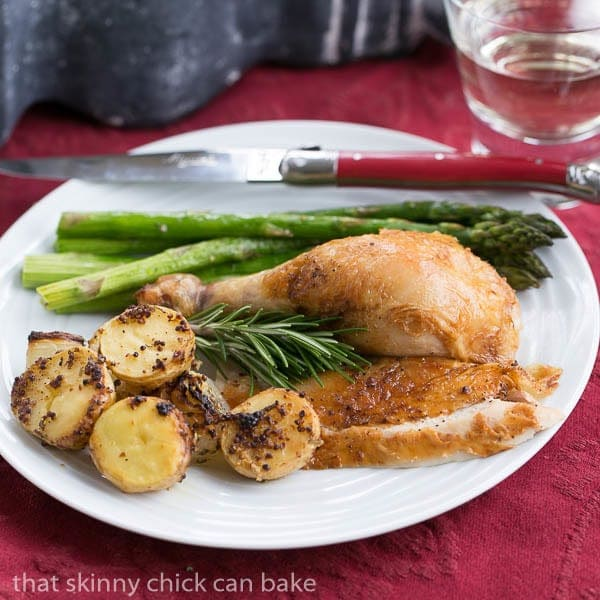 Classic Roast Chicken with Mustard Potatoes on a white dinner plate