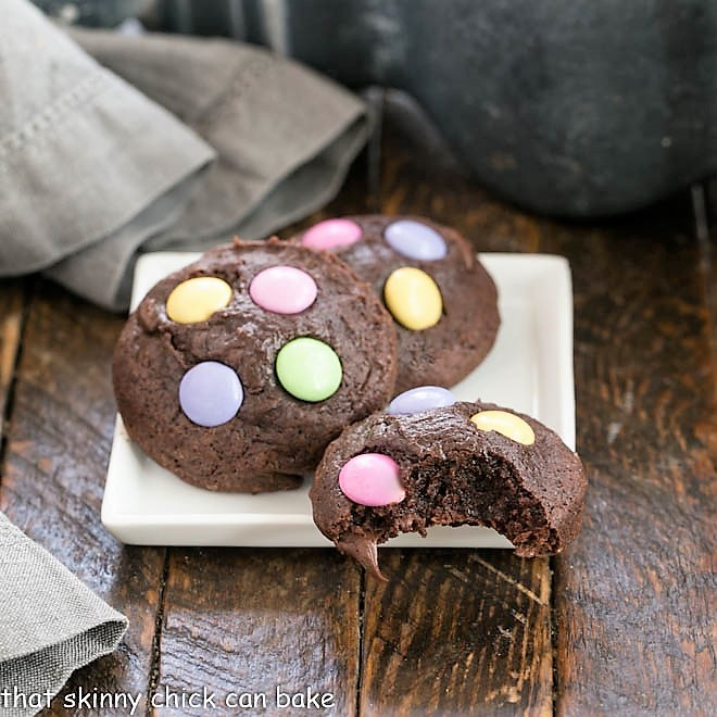 3 Brownie Cookies on a square white plate, one with a bite removed