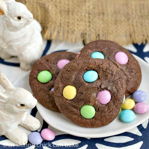 Easter Candy Brownie Cookies on a white dessert plate surrounded by wooden bunnies and Easter candies