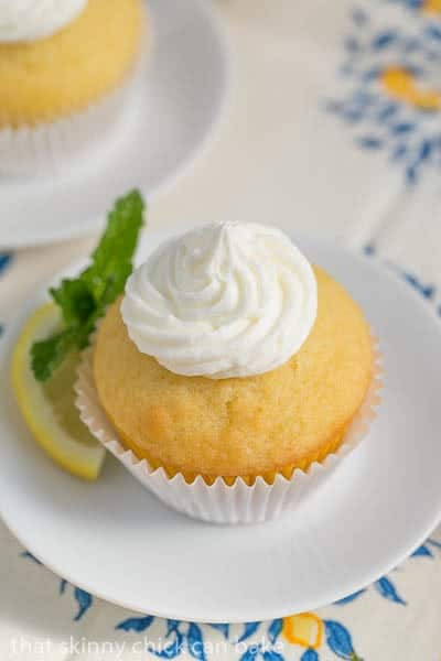 Limoncello Cupcake on a round white plate with a lemon and mint garnish