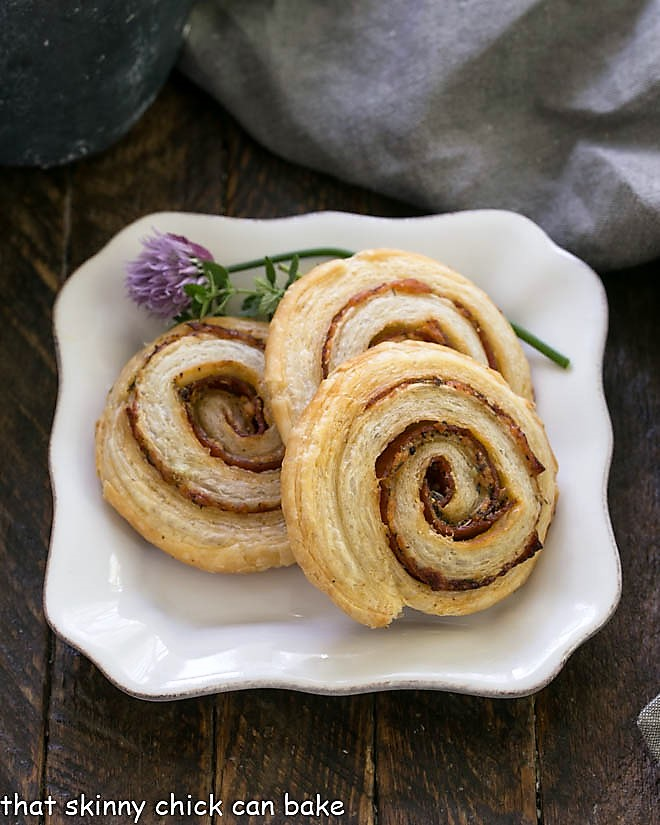 Honey Mustard Pepperoni Pinwheels on a square white plate garnished with flowering chives