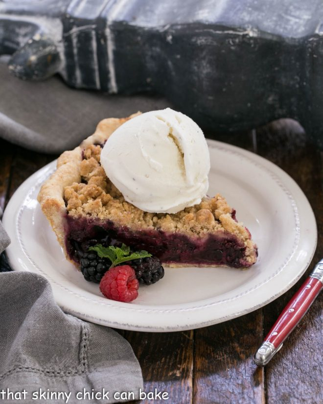 Slice of raspberry pie a la mode on a white dessert plate