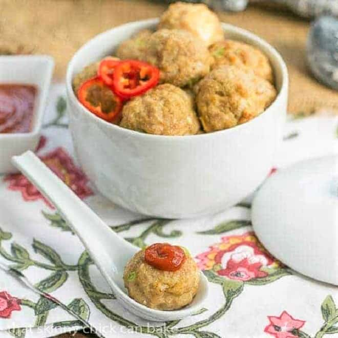 Sesame Ginger Meatballs in a white ceramic bowl with one topped with sriracha in a white ceramic spoon