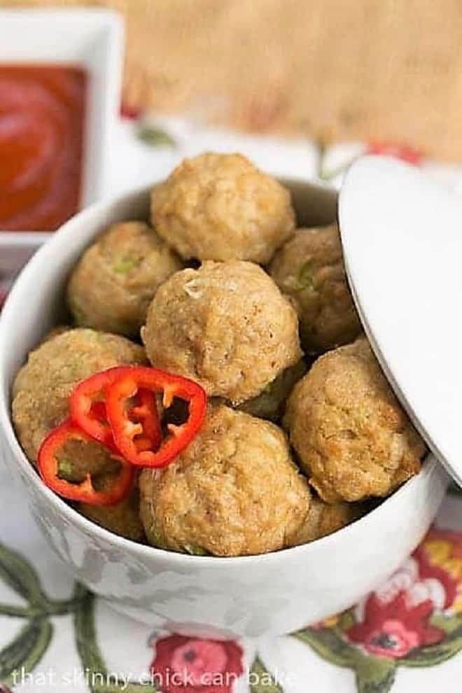 Sesame Ginger Meatballs in a white lidded serving dish