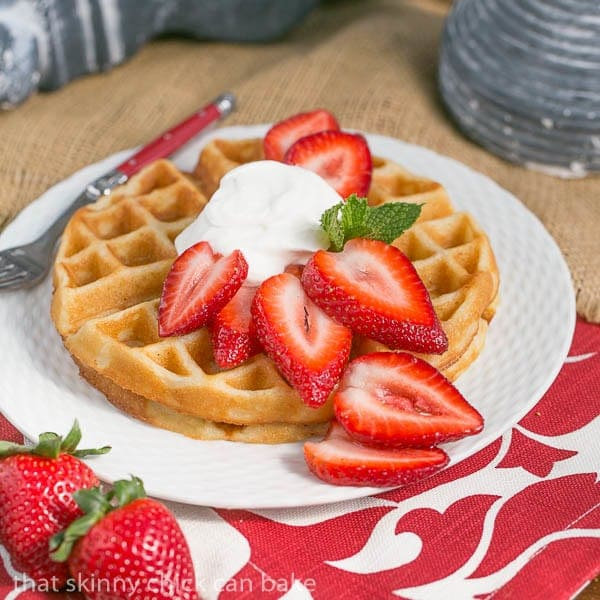 Belgian Waffles and Cream Dessert on a white plate topped with strawberries