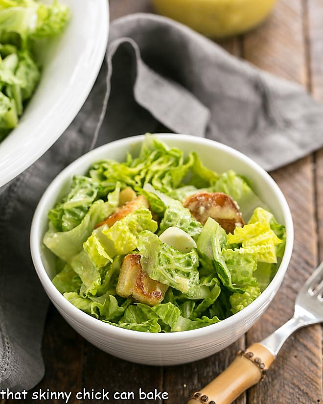 Caesar Salad Recipe in a small white salad bowl with a bamboo handled fork