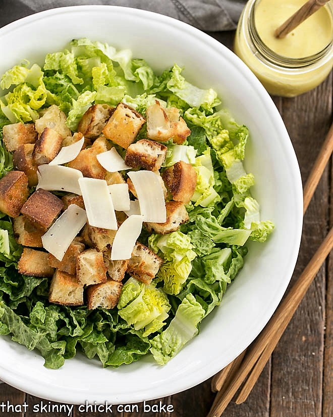 Caesar Salad Recipe from above in a white serving boql with wooden tongs and jar of salad dressing