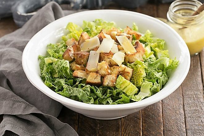 Side view of Caesar Salad in a white serving bowl for featured image