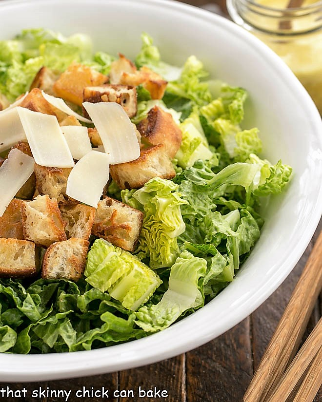 Close view of undressed Caesar salad in a white serving bowl