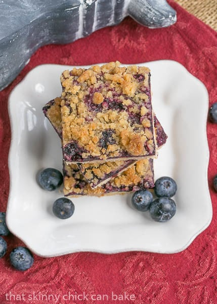 Overhead view of a stack of Blueberry Streusel Bars on a square white plate