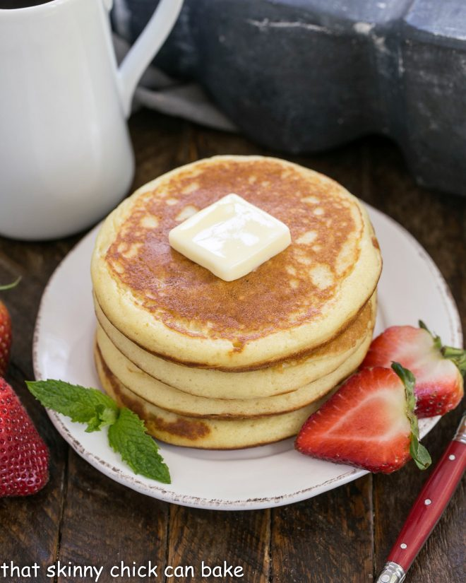 Classic Buttermilk Pancakes stacked on a white plate and garnished with sliced strawberries