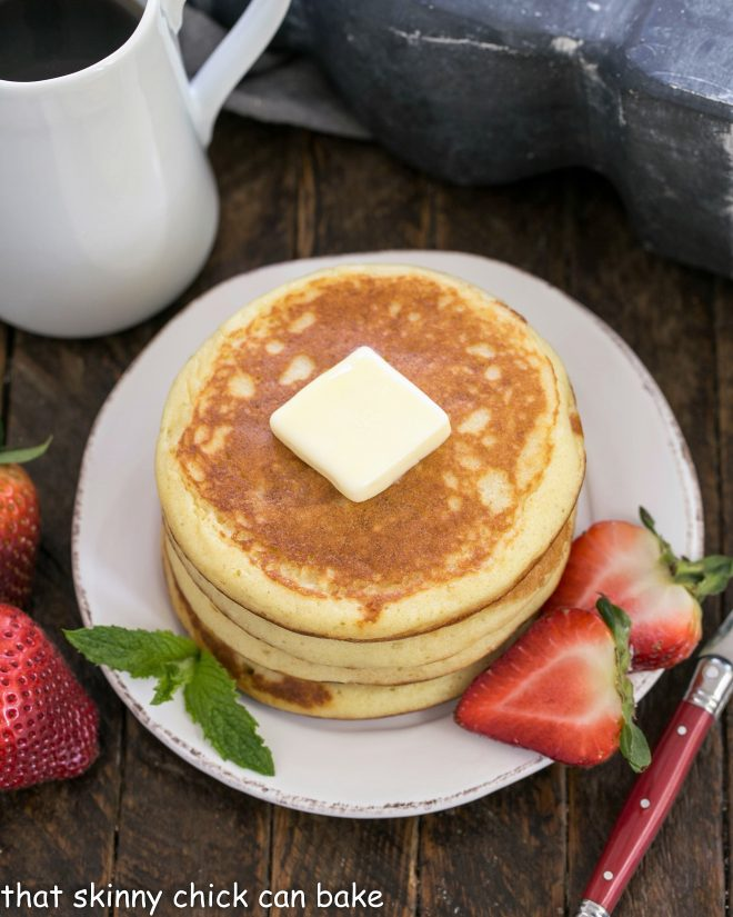 A stack of buttermilk pancakes topped with a pat of butter and served with sliced berries