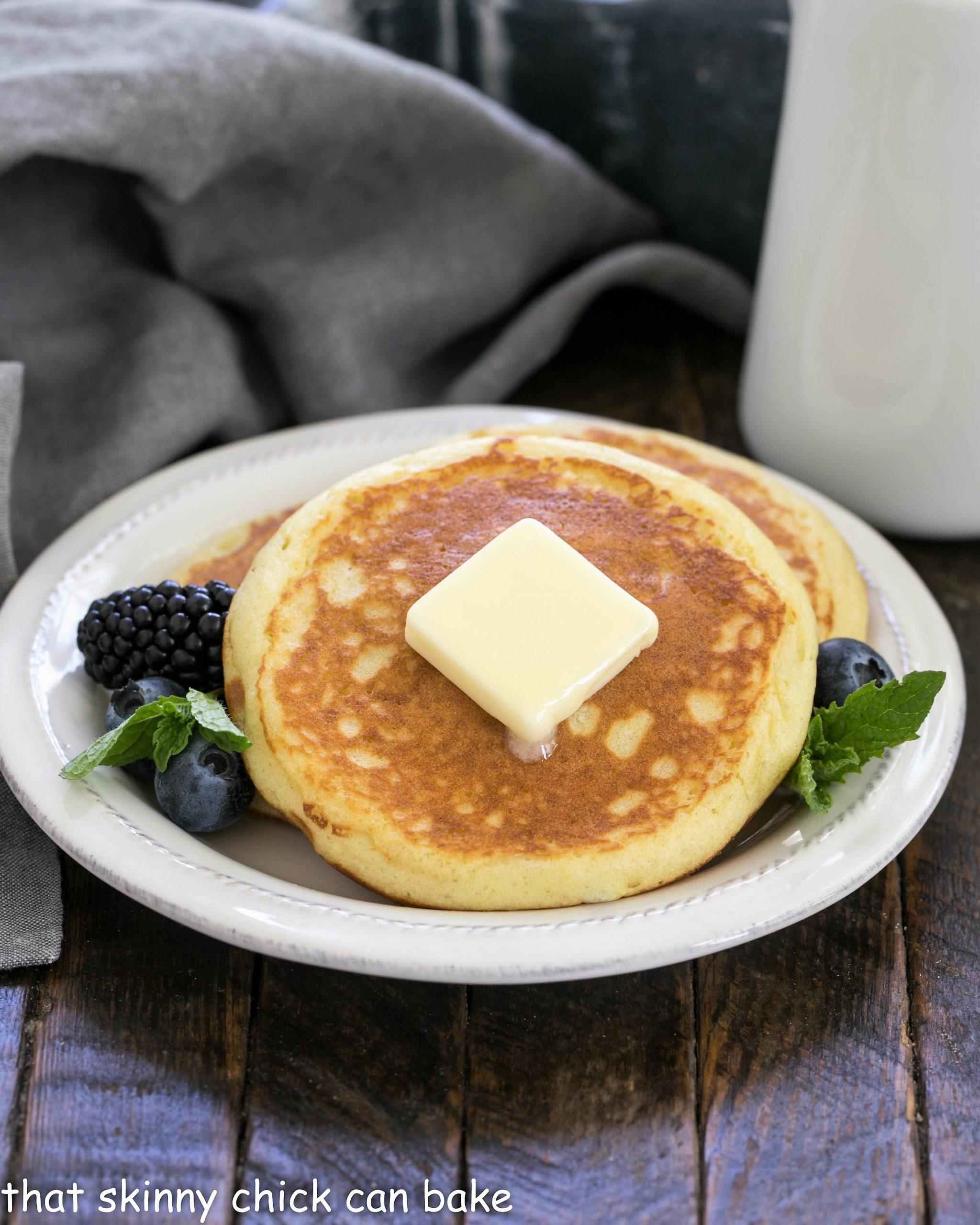 Buttermilk pancakew on a small white plate topped with butter and served with berries and mint