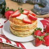 Stack of Classic Buttermilk Pancakes on a white plate topped with strawberries and butter