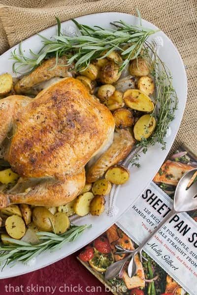 Classic Roast Chicken with Mustard Potatoes on a white platter with cookbook