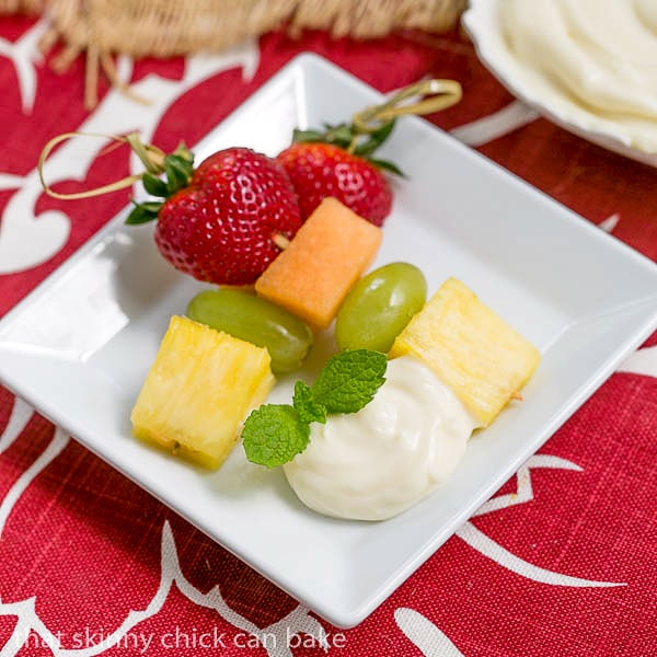 Fruit Kebabs with White Chocolate Mascarpone Dip on a small square plate with a dollop of dip and a sprig of mint