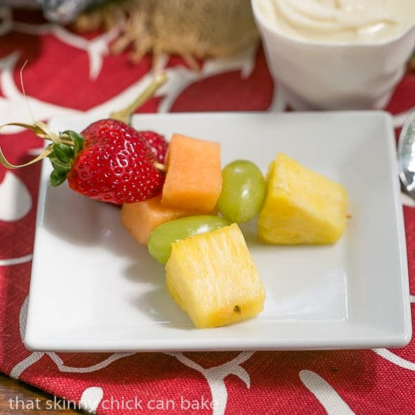 Two Fruit Kebabs with White Chocolate Mascarpone Dip on a square white plate
