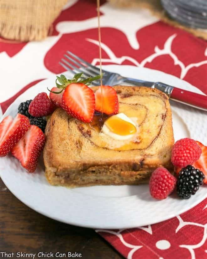 Overnight Cinnamon Bread French Toast with a drizzle of maple syrup on a white plate