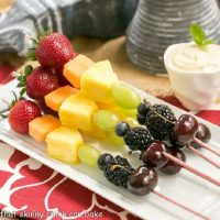 Rainbow fruit kabobs on a white ceramic tray