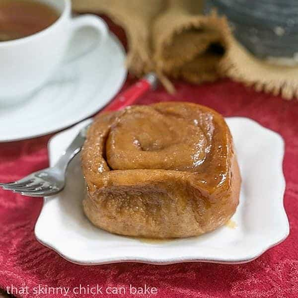 Cinnamon Sticky Buns on a white plate with a red handled fork