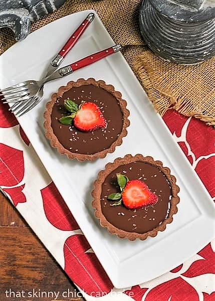 Two Double Chocolate Tartlets on a white rectangular platter with two red handled forks