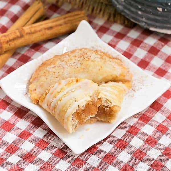 Two Fried Apple Pies on a white ceramic plate on a checkered napkin, with one broken open to expose the filling
