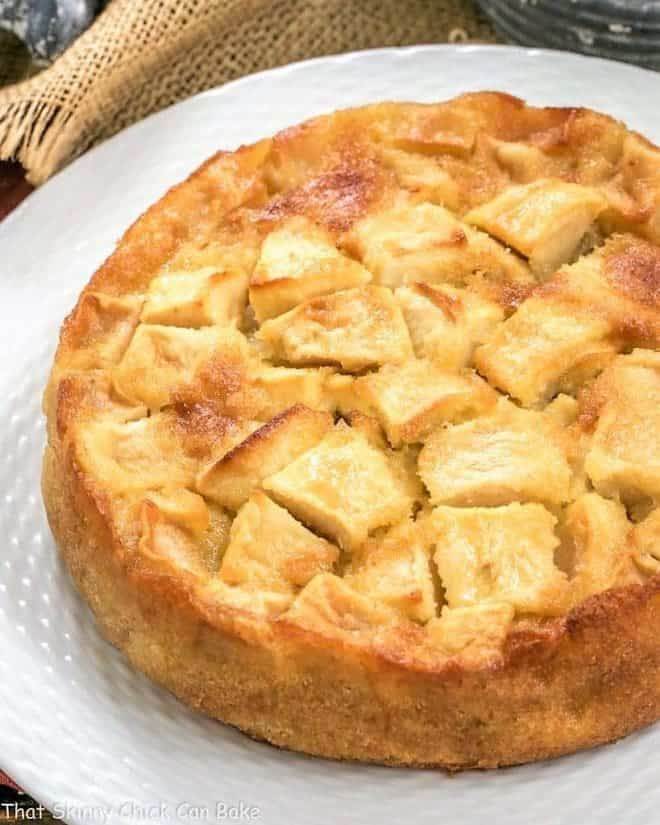 French Apple Cake on a white cake plate with a basketweave edge