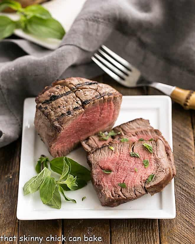 Grilled Steak with Garlic Butter on a square white plate garnished with herbs